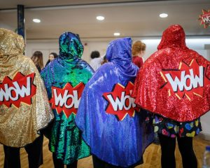 Four sparkly WoW capes being modelled here by four volunteers.