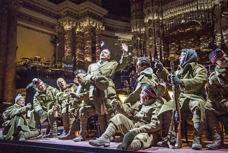 Adrian Clarke as Father Palmer with members of the Chorus of Opera North as the Scottish troops in Opera North's production of Silent Night by Kevin Puts [Photo credit: Tristram Kenton]