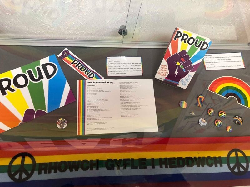 Colourful collection of paraphernalia surrounding an anthology PROUD by Juno Dawson and featuring poem, How to come out as gay by Dean Atta