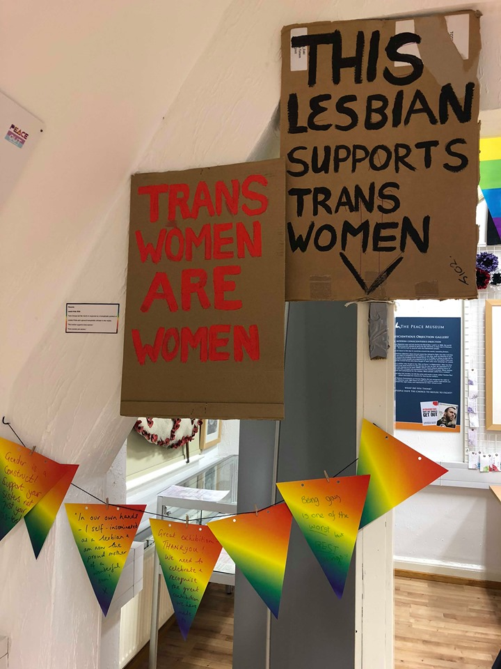 Handmade placards demonstrating support for trans women and bunting featuring visitor insights on LGBTQ+ culture