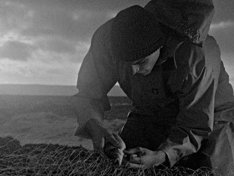 Still from the Early Day Films production, Bait (fisherman fixing his nets).