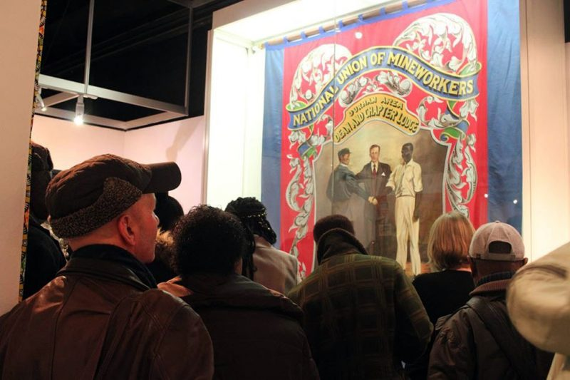 Digging Deep - Visitors look at NUM banner featuring African Caribbean mineworkers